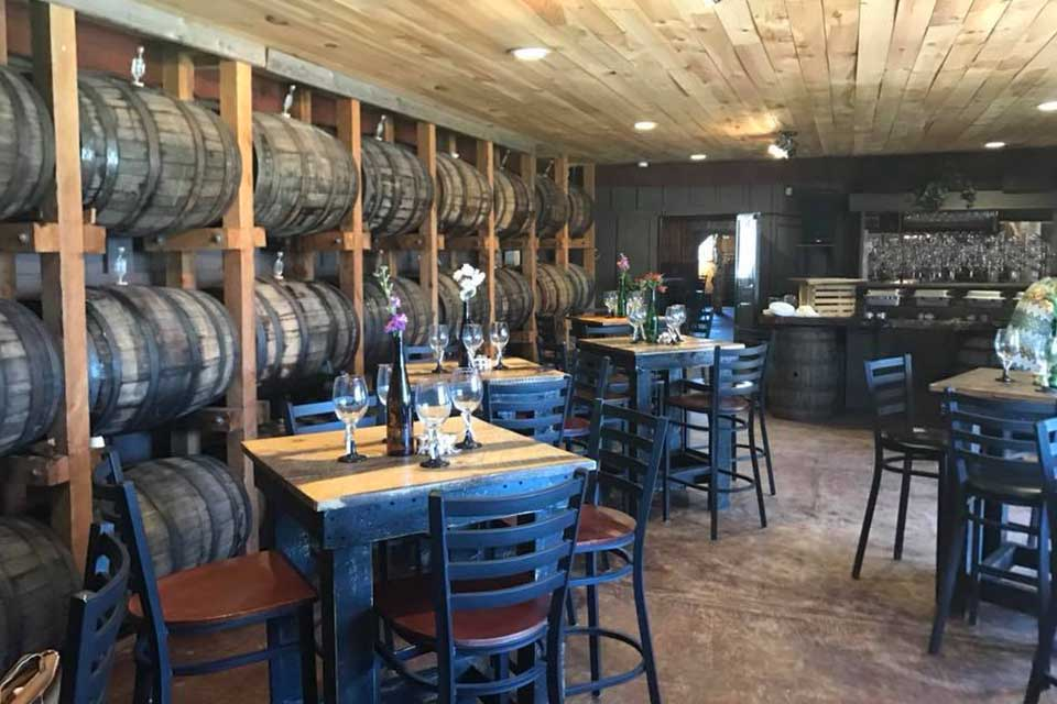 empty tables in room with barrels on walls