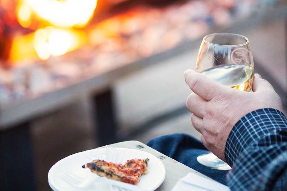 close up of man holding a wine glass and slice of pizza in front of firepit