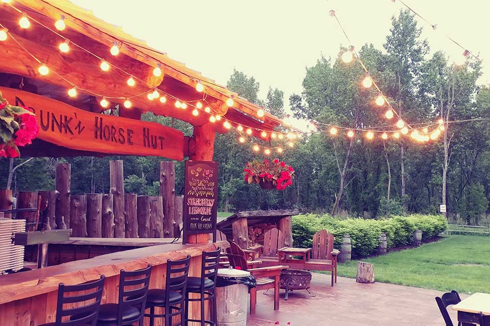 outdoor bar area lit up at dusk with string lights