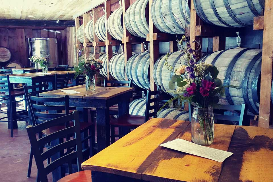 High top tables and wine barrels on wall